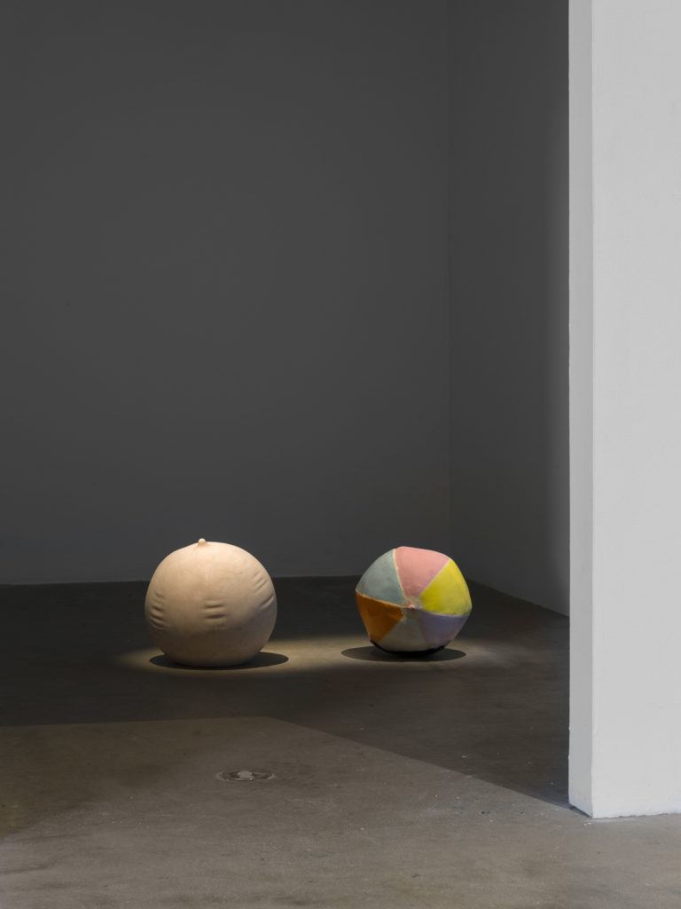 This is a color photograph of two sculptures by Nevine Mahmoud. The sculpture on the left is Ball Stripped Bare, which is spherical, made of Portuguese pink marble, and resembles an inflated beach ball. To the right of this work is Deflating Beach Ball II, which is slightly smaller in comparison to the other work and is made of ceramic with a multicolored in colors of pink, light blue, yellow and orange glaze mimicking the look of a slightly deflated beach ball. Both sculptures are placed directly on the floor and side-by-side.