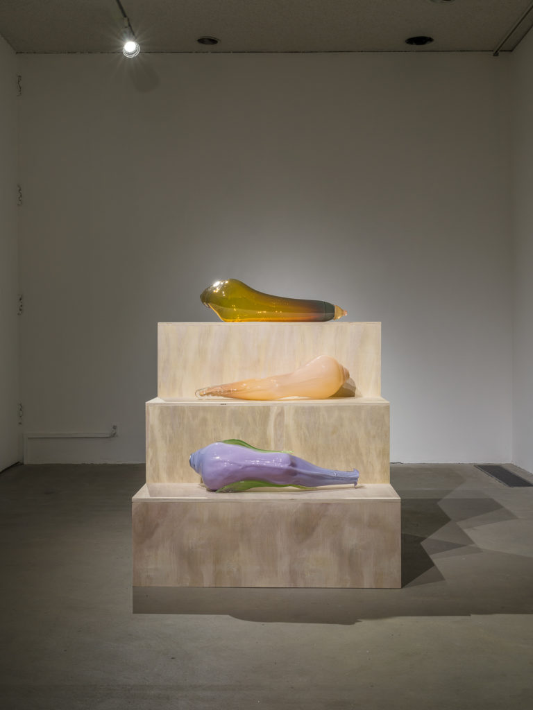 This is a color photograph of three large blown glass sculptures of roughly equal size by Nevine Mahmoud resting on a tiered, wooden three step pedestal. At the top is a sculpture entitled yellow Toy, an amber colored blown glass piece resembling a human leg. On the center tier is a sculpture entitled Leg (Lila), a flesh toned blown glass piece resembling a human leg. Beneath this on the last tier is another leg shaped work called Leg (lilac), made of lilac and green colored blown glass.